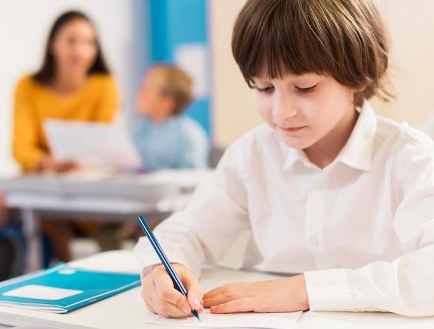 Kid schrijven in zijn notitieblok tijdens de les