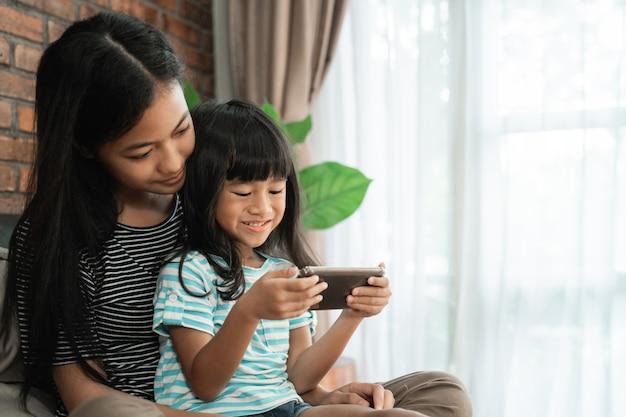 Kid speelspel met zus op slimme telefoon