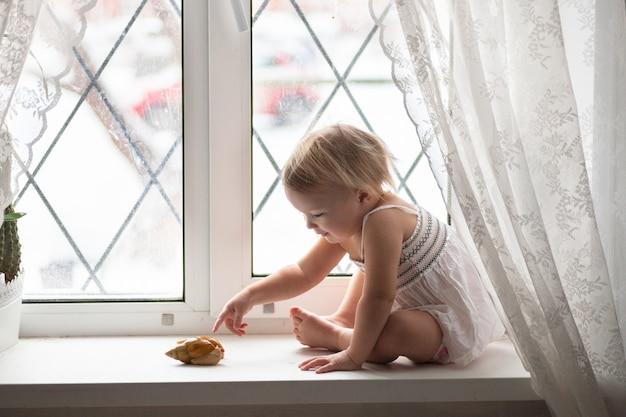 Kid speelt met grote slak op raam echt interieur, levensstijl, softfokus, het concept van kindertijd en dieren