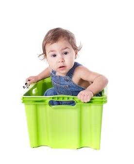 Kid speelt met plastic container geïsoleerd op wit