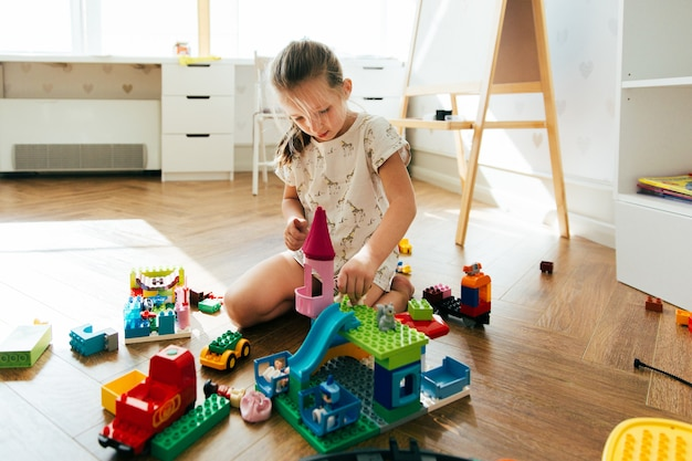 Kid spelen met kleurrijke blokken. meisje de bouwtoren van blokspeelgoed. educatief en creatief speelgoed en spelletjes voor jonge kinderen. speeltijd en rommel thuis