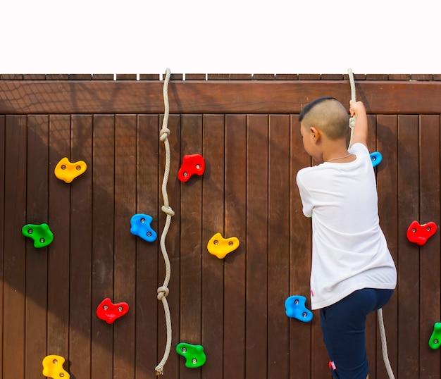 Kid spelen rotsklimmen simulatie buiten