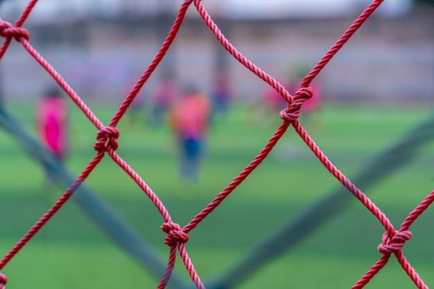 Kid traint voetbalvoetbal achter het net voor sporttraining en voetbalacademieconcept.