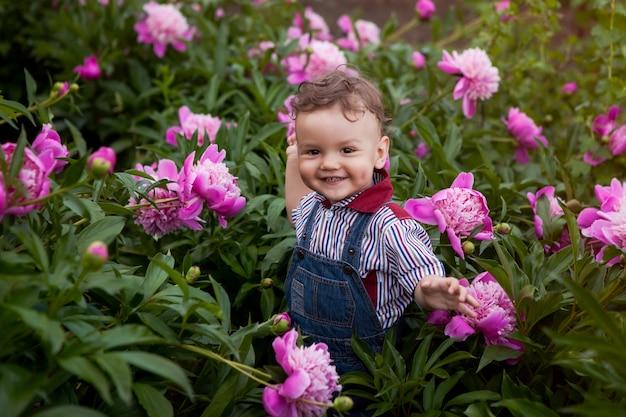 Kid tuin in roze pioenrozen, een geschenk voor moeder verzamelt een boeket bloemen.