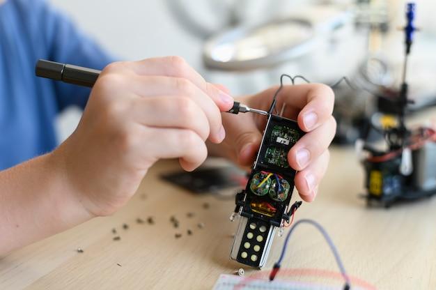 Kid-uitvinder assembleert radiobesturingsrobot close-up met gereedschap en doe-het-zelfrobot