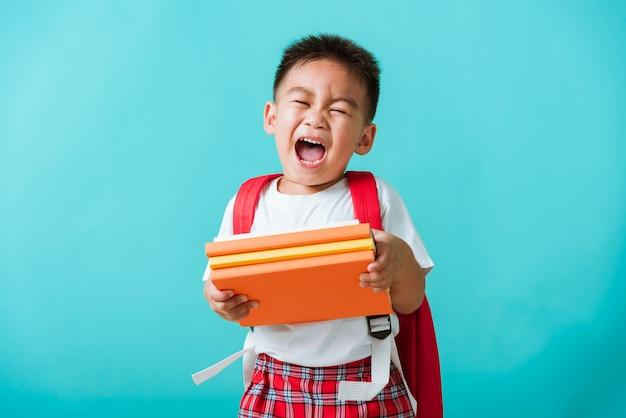 Kid van voorschoolse kleuterschool met boek en schooltas