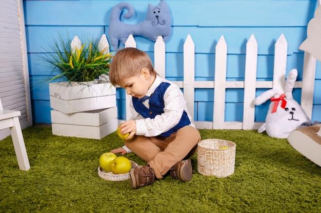 Kid verzamelt herfst herfst oogst. portret van schattige grappige jongen. picknick in de natuur. leuke grappige kleine jongen met rieten mand.