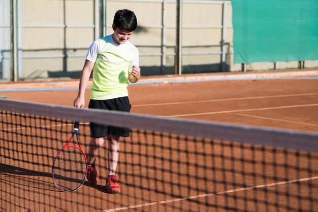 Kid viert de overwinning van een tennisspel