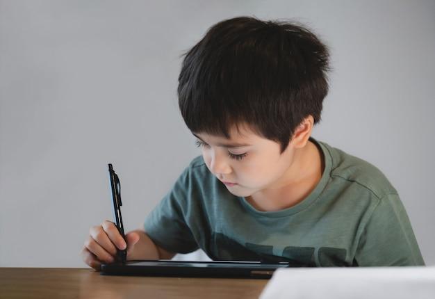 Kid zelfisolatie met behulp van tablet voor zijn huiswerk