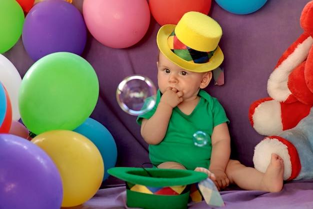 Kid zit in een leuke feestelijke sfeer met ballonnen en kijkt naar zeepbellen.