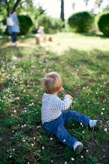 Kid zit op een bloemenweide met een stok in zijn hand en draait zich om