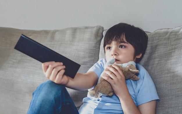 Kid zittend op de bank met afstandsbediening en tv kijken