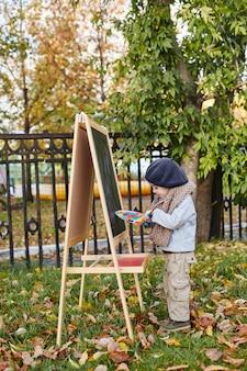Kids baby in retro herfst lente kleding. klein kind zit glimlachend in de natuur, sjaal om zijn nek, koel weer. heldere emoties op zijn gezicht. rusland, sverdlovsk, 29 september 2018