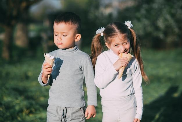 Kids jongen en meisje buiten eten van ijs op gras en bomen achtergrond erg lief