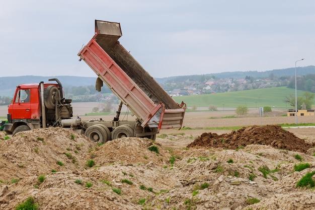 Kiepwagen lossen grond of zand op bouwplaats