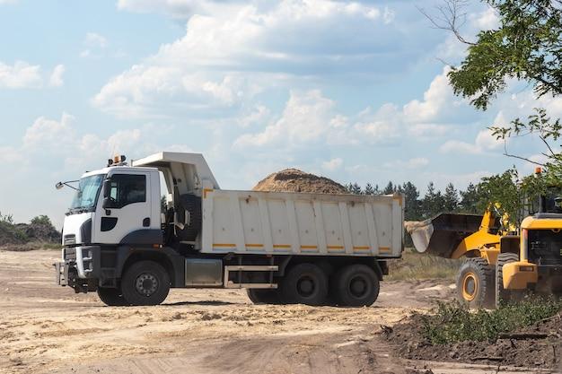 Kiepwagen met bos land achterin en graafmachine op de bouwplaats buiten de stad
