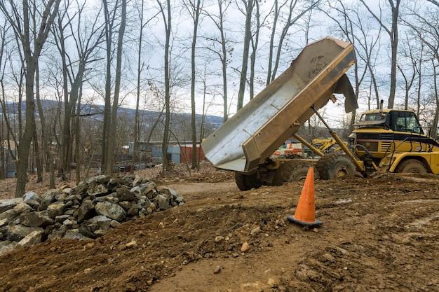 Kiepwagens vervoeren voor het verwerken van steen die een tractor met steen uploadt