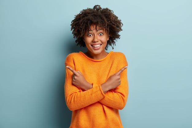 Kies een ding. optimistische donkere vrouw met blije uitdrukking, zegt dat beide keuzes geweldig zijn, kruist handen over de borst, wijst naar verschillende kanten, draagt oranje casual trui, geïsoleerd op blauwe muur