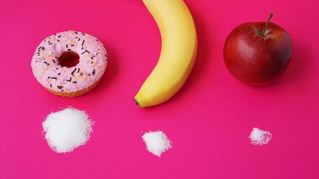 Kies gezond fruit in plaats van ongezonde snoepjes met een enorme hoeveelheid suiker - roze achtergrond