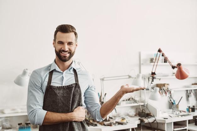Kies het. portret van een vrolijke mannelijke juwelier die een schort draagt terwijl hij in zijn sieradenstudio staat. bedrijf. sieraden workshop
