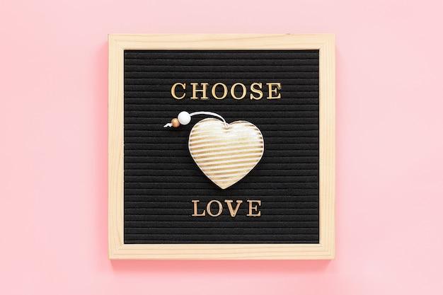 Kies liefde. motiverende citaat in gouden letters en textiel hart op zwarte letter boardstcard. bovenaanzicht