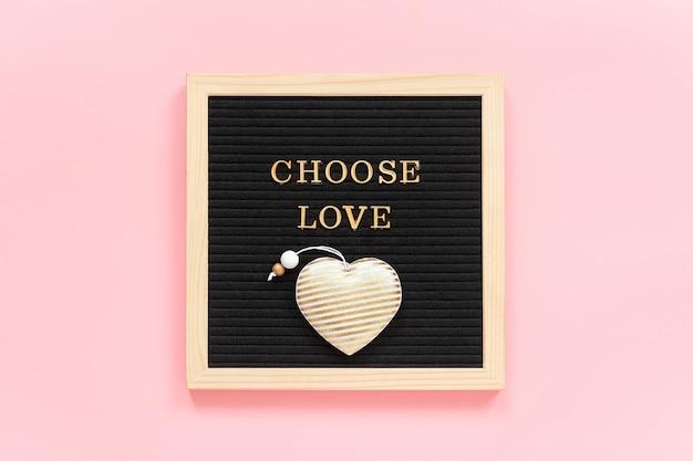 Kies liefde. motiverende citaat in gouden letters en textiel hart op zwarte letter bord op roze achtergrond.