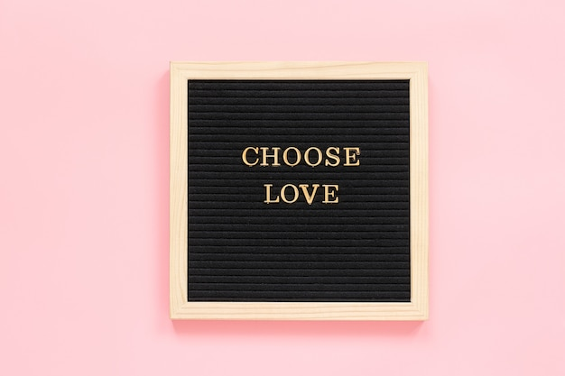 Kies liefde. motiverende citaat in gouden letters op zwart letterbord op roze achtergrond