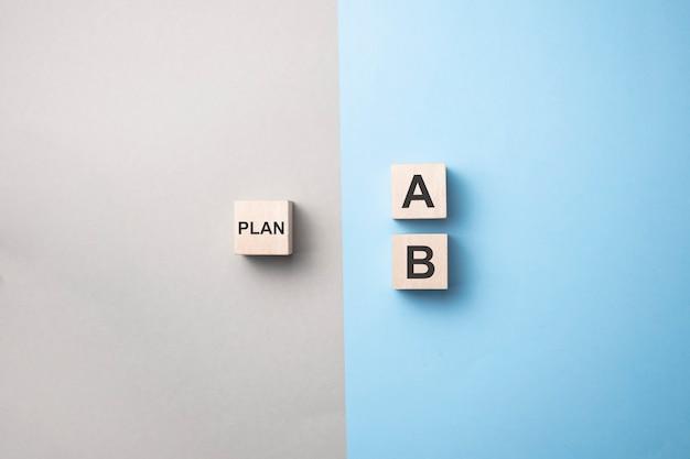 Kies met de hand een houten kubus met het woord plan a tot plan b op blauw