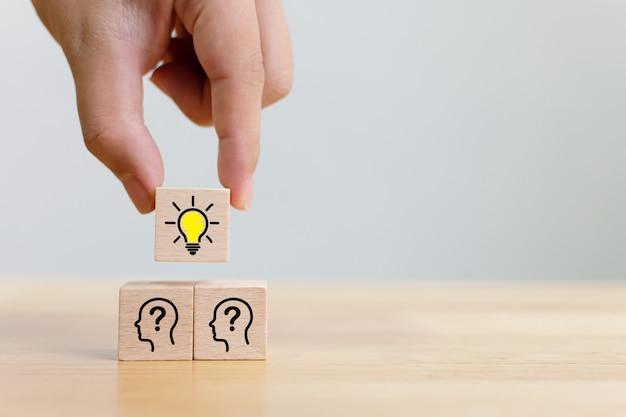Kies met de hand een houten kubusblok met gloeilamp en hoofd menselijk pictogram