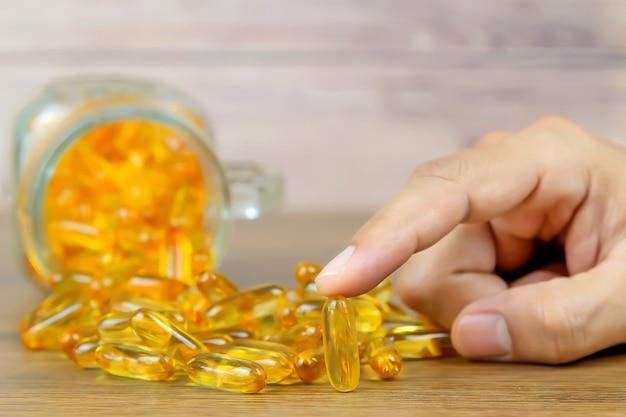 Kies met de hand een levertraancapsule uit een stapel levertraan of visolie-voedingssupplement voor gezondheidsconcepten.