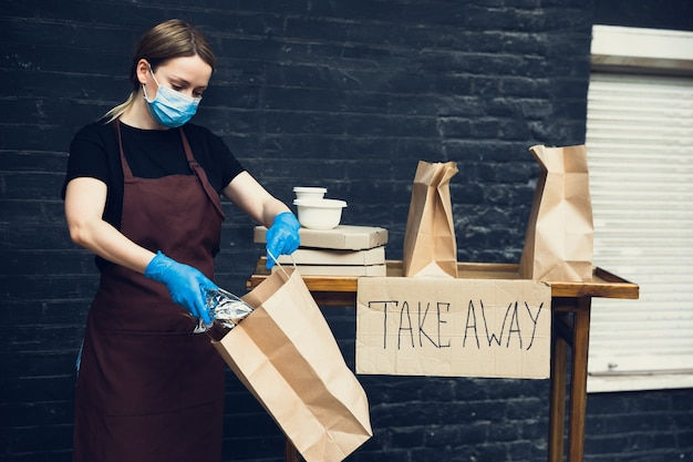 Kies voor gezondheid. vrouw die drankjes en maaltijden bereidt, een beschermend gezichtsmasker draagt, handschoenen. contactloze bezorgservice tijdens quarantaine coronavirus pandemie. afhaalconcept. recyclebare mokken, pakketten.