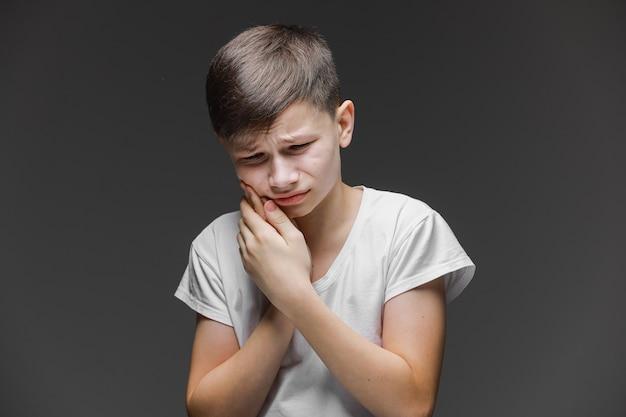 Kiespijn bij kinderen. zijn wang vasthouden, tandpijn. closeup portret jongen met gevoelige tand. geïsoleerde grijze muur achtergrond. negatieve menselijke emotie, gezichtsuitdrukking gevoel reactie.