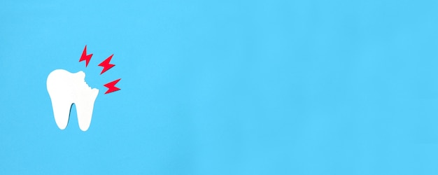 Kiespijn concept. papieren tandbeeldje en gele bliksem op een blauwe achtergrond.