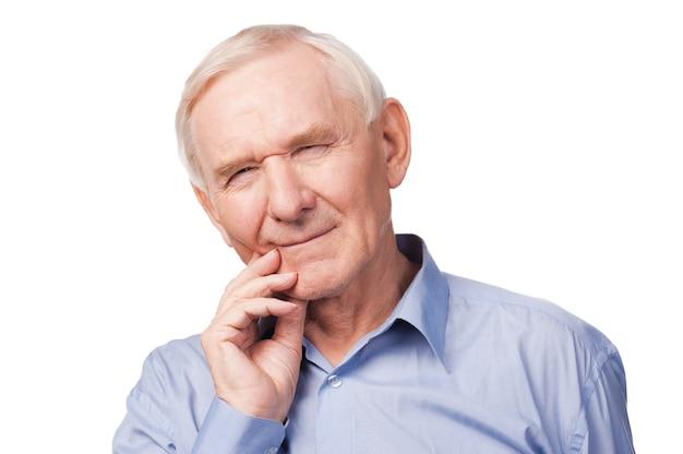 Kiespijn. gefrustreerde senior man in shirt die hand op zijn wang houdt en ogen dicht houdt terwijl hij tegen een witte achtergrond staat