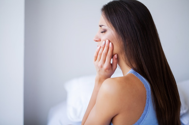 Kiespijn. tandheelkundige zorg en kiespijn. vrouw gevoel tandpijn. close-up van mooi droevig meisje die aan sterke tandpijn lijden. aantrekkelijke vrouw gevoel pijnlijke kiespijn. tandheelkundige gezondheid en verzorging