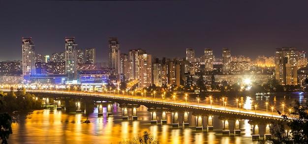 Kiev (kiev) stad, de hoofdstad van oekraïne 's nachts naast de rivier de dnipro (dniepr) met weerspiegeling in water