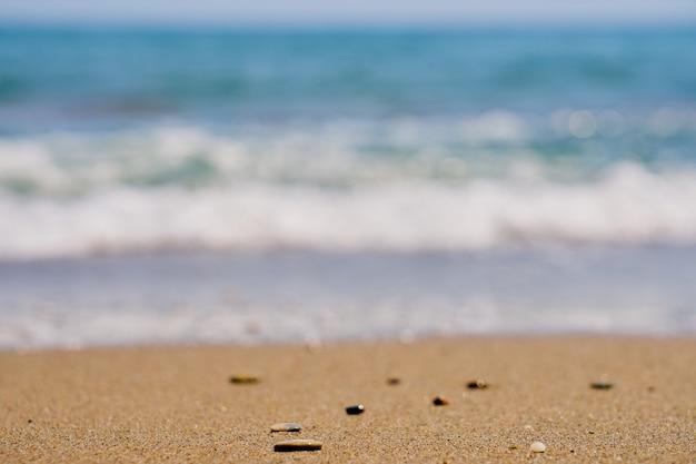 Kiezelsteen op tropisch strand met vage golven op de achtergrond.