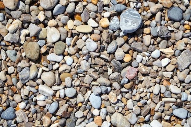 Kiezelstenen op het strand. gladde stenen in verschillende maten en kleuren. bovenaanzicht