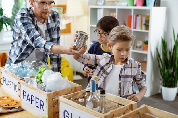 Kiezen voor container. attente bebaarde leraar in een heldere bril die metalen blikjes voorstelt en ernaar vraagt, plaats in het recyclingsysteem