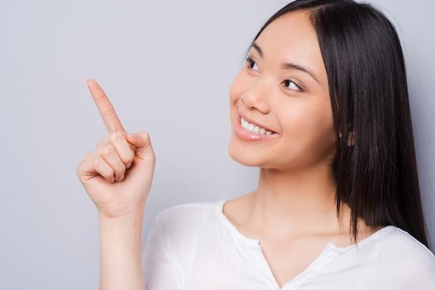 Kijk daar maar eens naar! mooie jonge aziatische vrouw die wegwijst en glimlacht terwijl ze tegen een grijze achtergrond staat