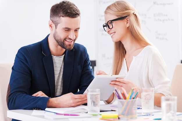 Kijk daar maar eens naar! twee zelfverzekerde zakenmensen in slimme vrijetijdskleding die samen aan tafel zitten en iets bespreken terwijl ze naar de digitale tablet kijken