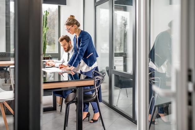 Kijk door de open deur op het luxe kantoorinterieur met zakenpaar aan het werk