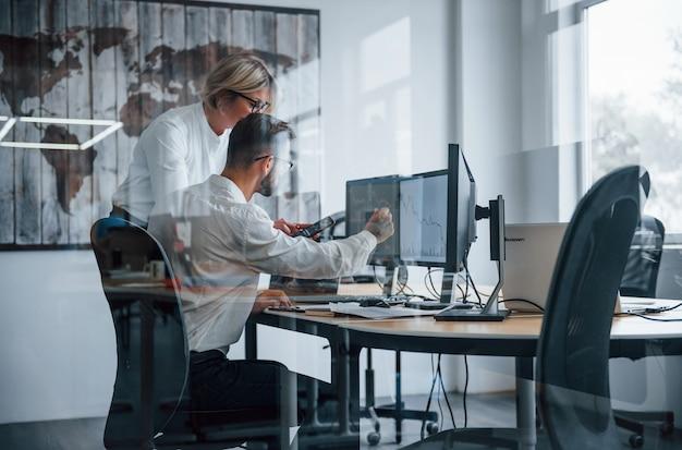 Kijk door het glas. twee effectenmakelaars in formele kleding werken op kantoor met financiële markt.