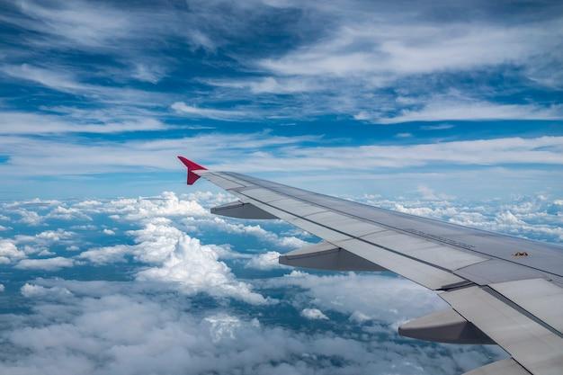 Kijk door het vliegtuigraam en de witte wolk en de blauwe lucht