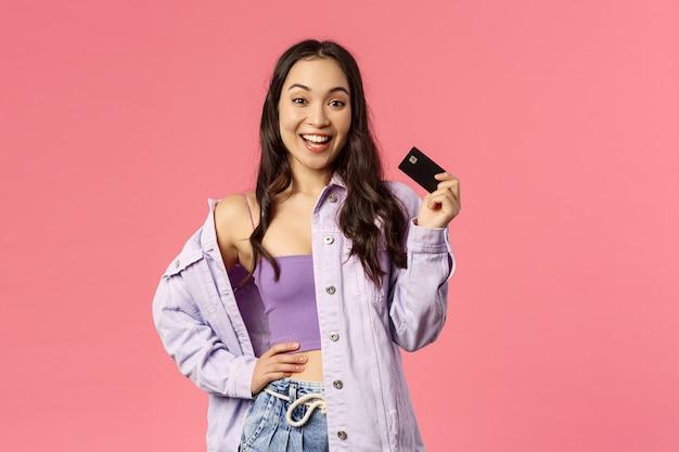 Kijk eens wat ik heb. portret van stijlvolle zorgeloos meisje, glimlachend en wuivende creditcard als vrienden vertellen shes kopen vanavond drankjes, klaar om te winkelen, onbezorgd over geld, roze achtergrond