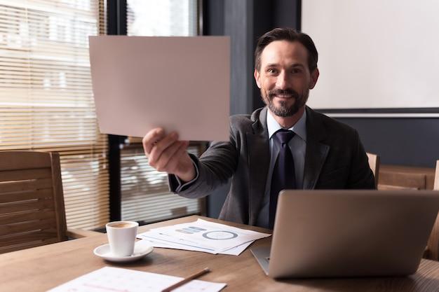 Kijk er naar. gelukkig knappe knappe man zit achter de laptop en lacht terwijl je een vel papier laat zien