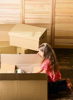 Kijk erin. gelukkig kind kartonnen doos. reparatie van de kamer. nieuw appartement. verhuisdozen uitpakken. aankoop nieuwe woning. kartonnen dozen - verhuizen naar een nieuw huis. gelukkig klein meisje in de kamer op dozen.