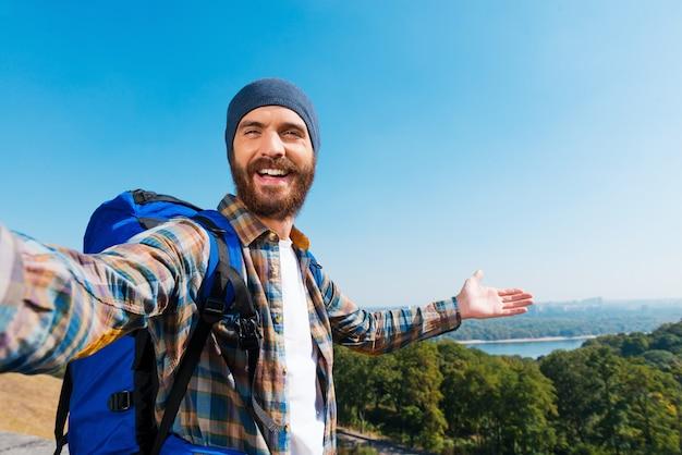 Kijk gewoon! ik ben hier! knappe jonge man die rugzak draagt en een foto van zichzelf maakt en naar het uitzicht wijst