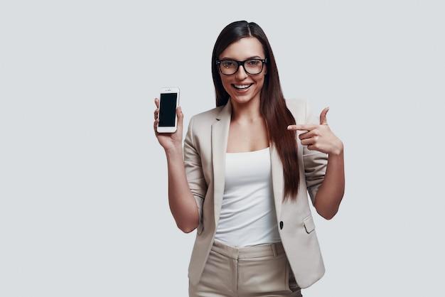 Kijk hier! aantrekkelijke jonge vrouw die kopieerruimte op de smartphone wijst en glimlacht terwijl ze tegen een grijze achtergrond staat