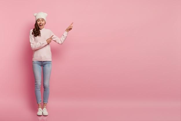 Kijk hier eens naar. blije positieve europese vrouw heeft lange krullen, wijst op vrije ruimte, is in een goed humeur, maakt reclame voor iets, draagt grappige hoofddeksels